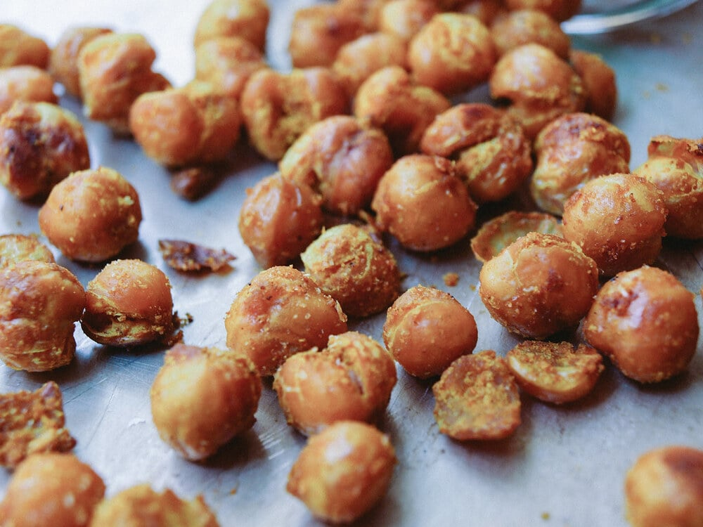 side angle view of freshly roasted chickpeas on a baking sheet.
