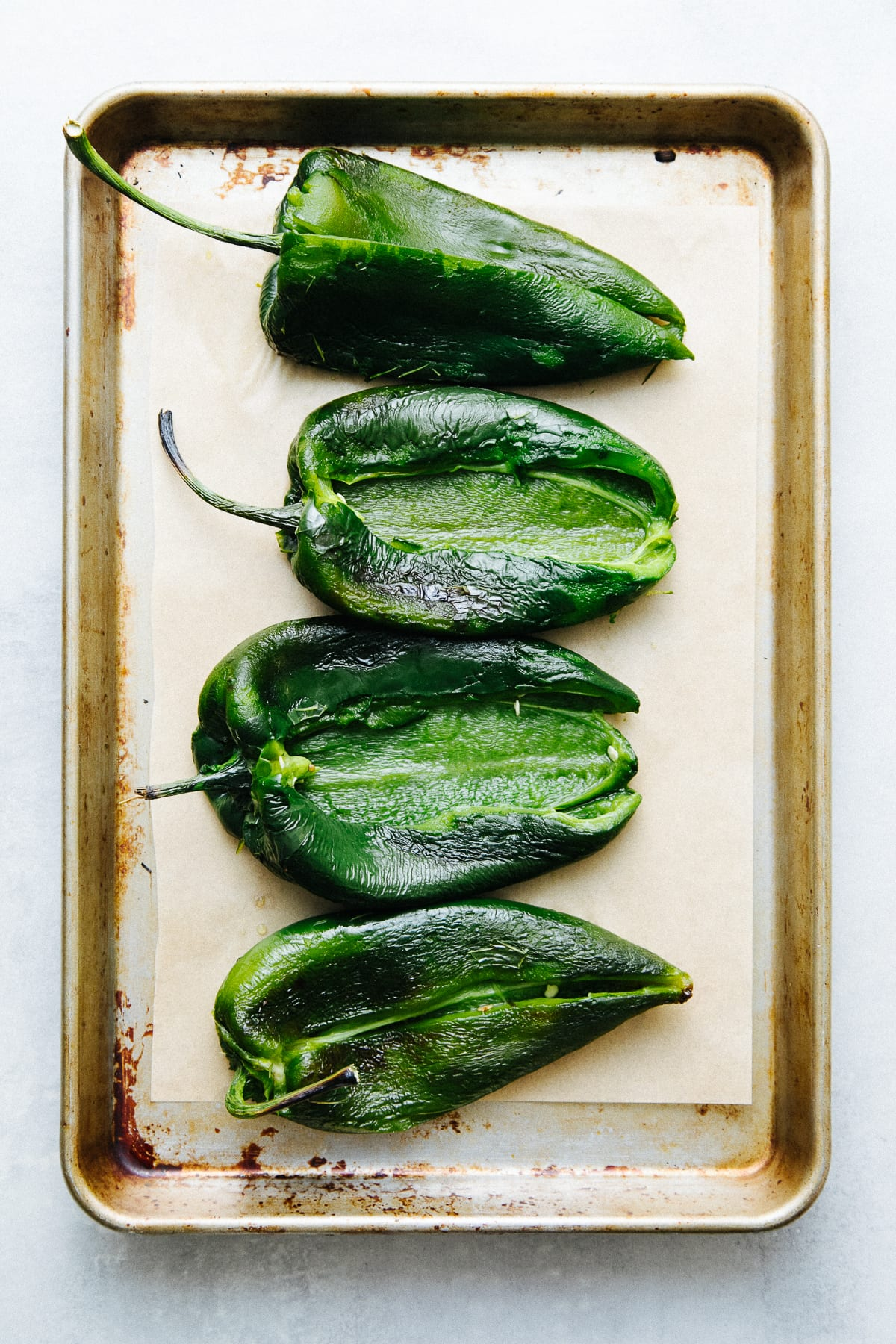 top down view of prepped roasted, peeled and de-seeded poblano peppers on a baking sheet.