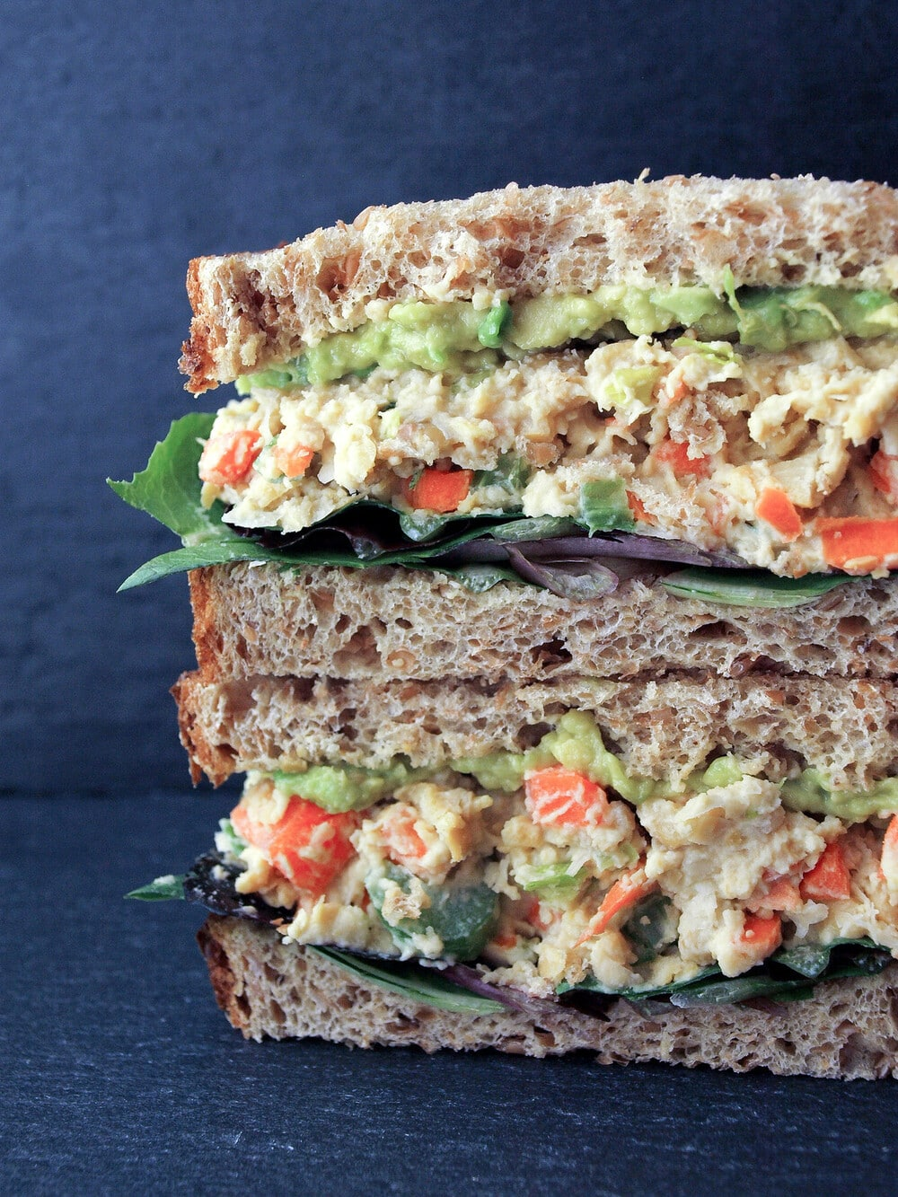 up close, head on view of a vegan mashed chickpea salad sandwich sliced in half and stacked.