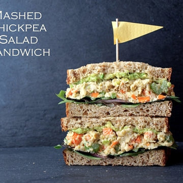 head on view of vegan mashed chickpea salad sandwich sliced in half and stacked.