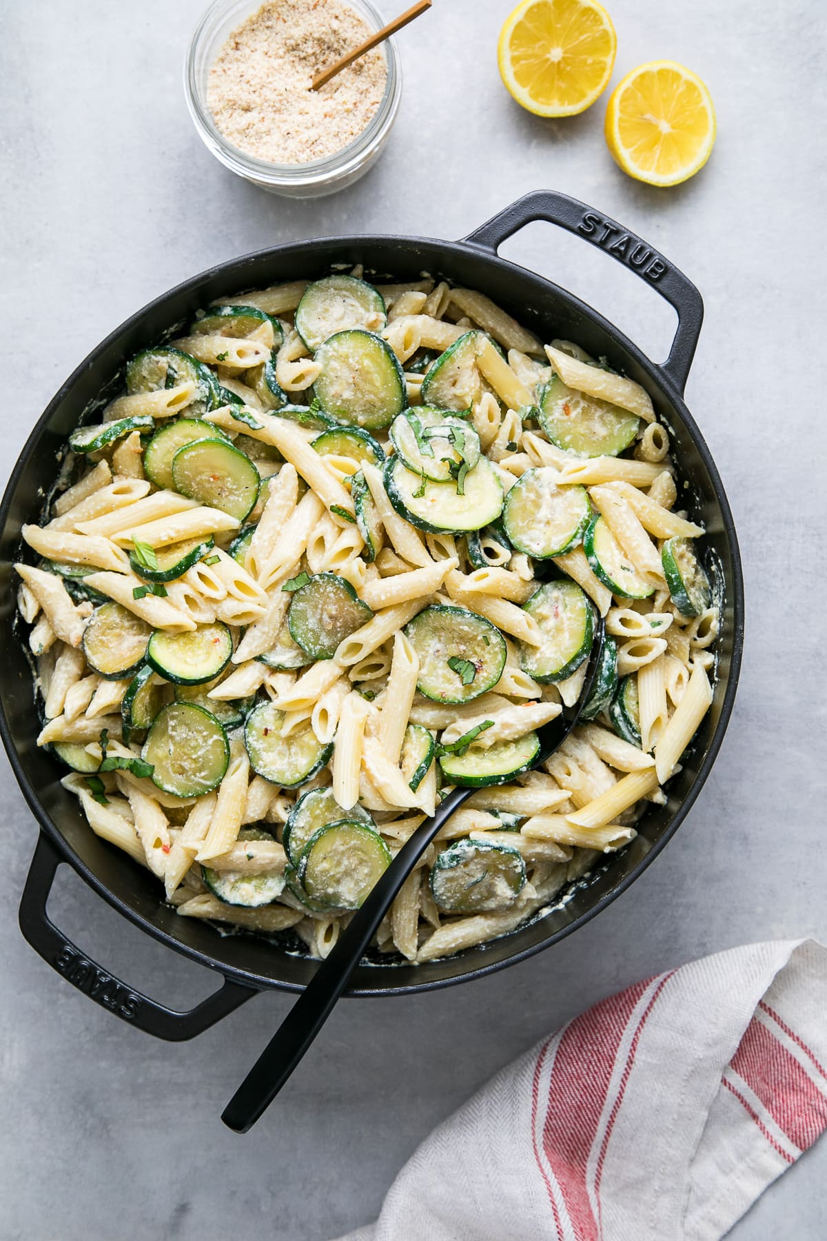 top down view of a pot with freshly made zucchini ricotta pasta with mint and basil.