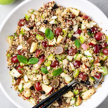 top down view of healthy vegan apple quinoa salad recipe with grapes, mint and sweet tahini dressing in a serving bowl.