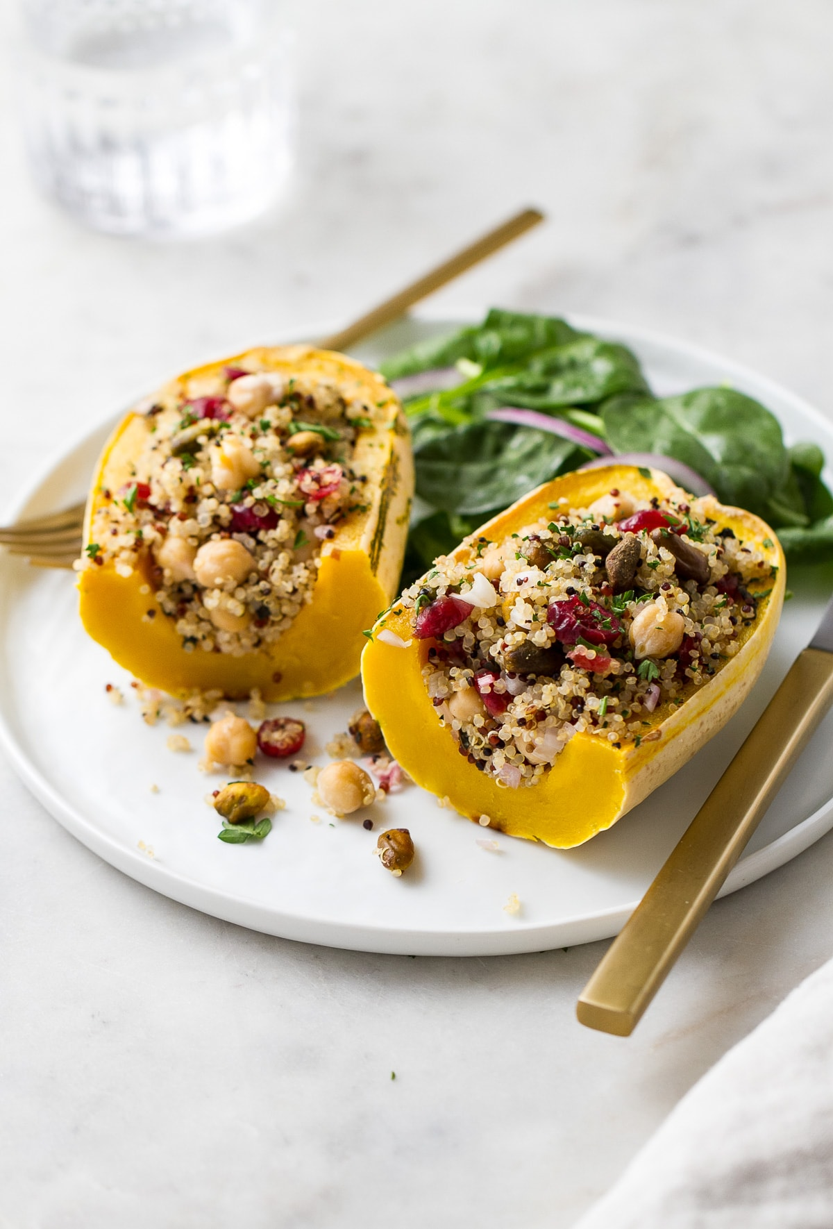 side angle view of stuffed delicata squash sliced in half on a white plate.