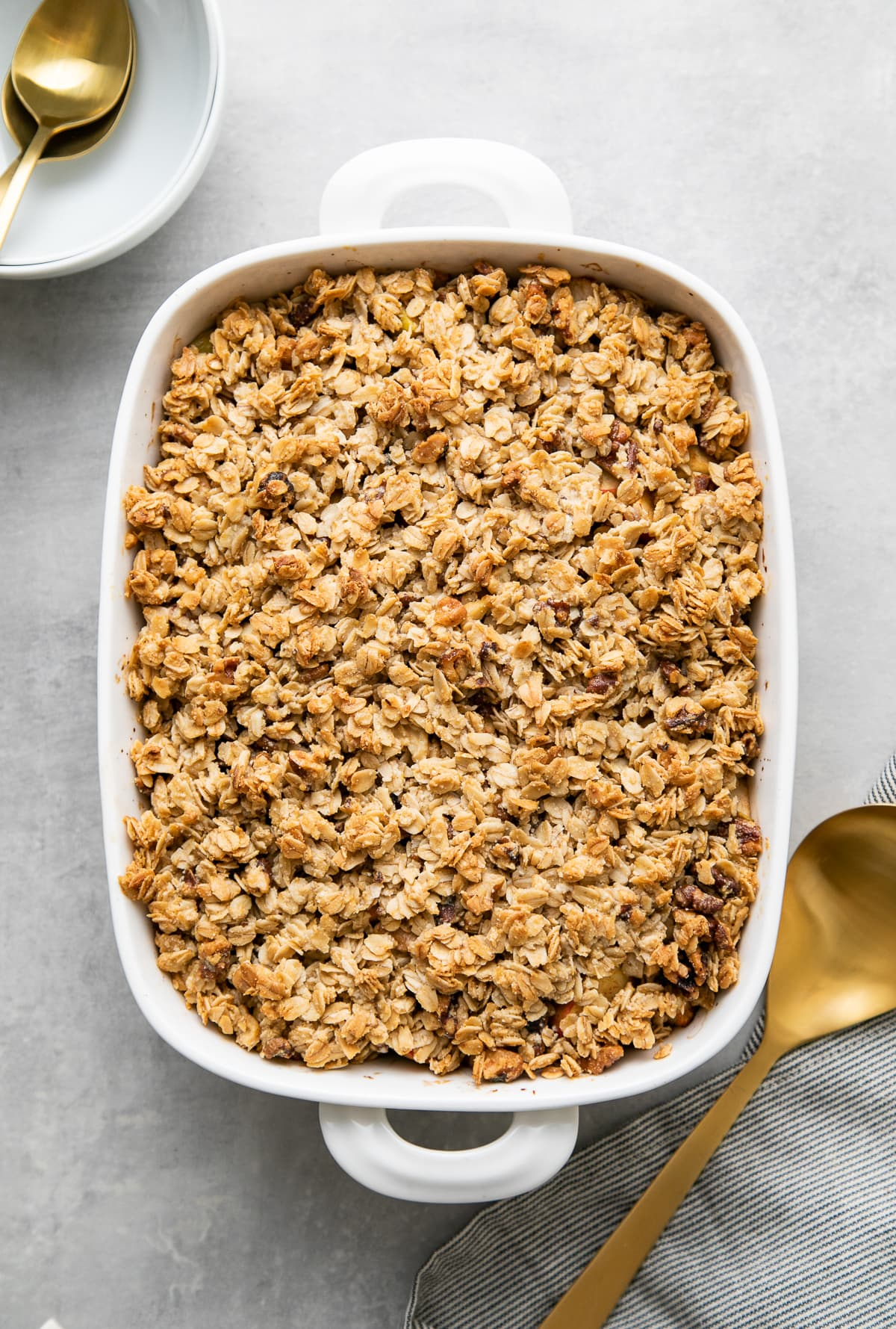 top down view of freshly made healthy apple crisp in a white baking dish.