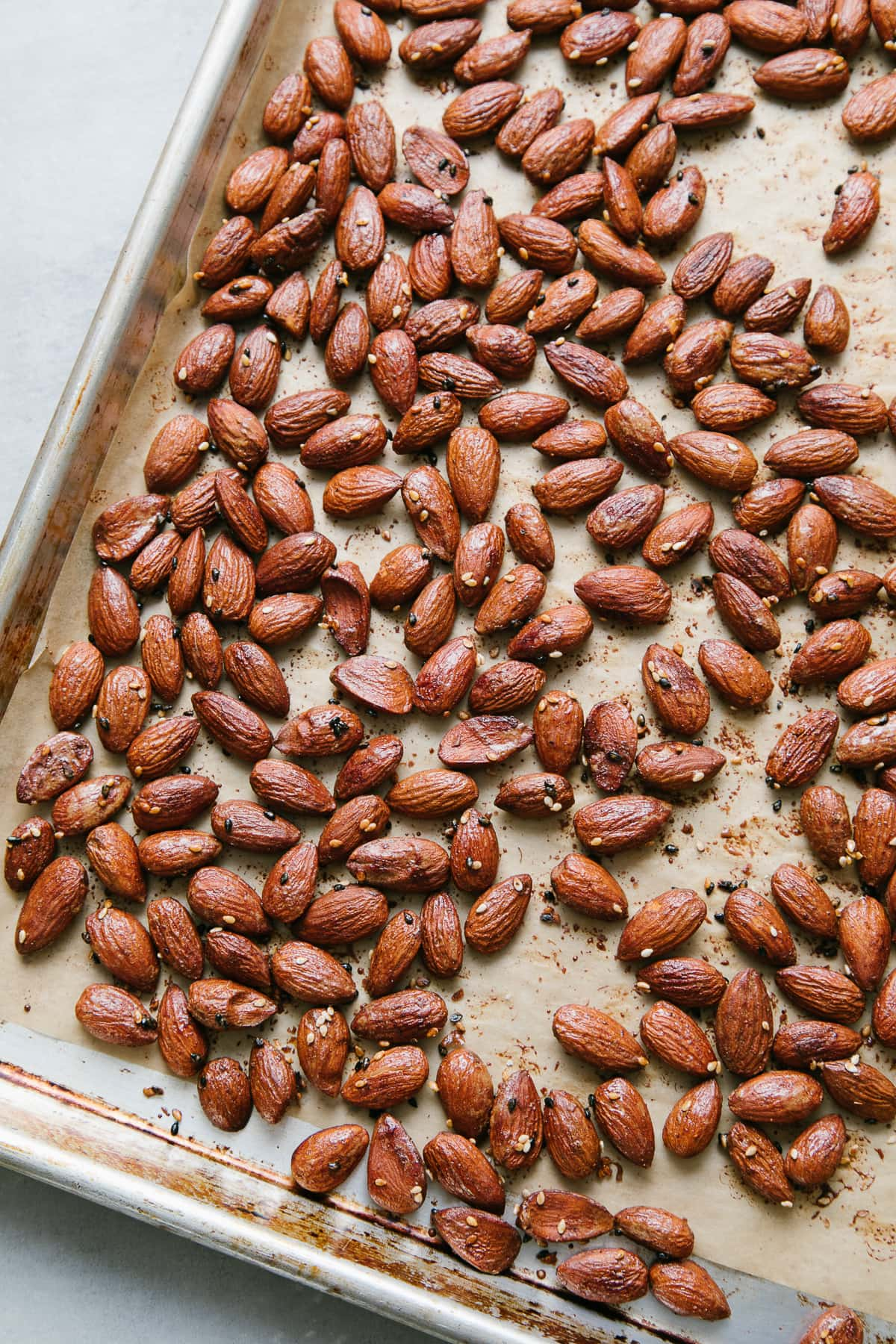 top down view of freshly made mirin maple roasted almonds on a baking sheet.