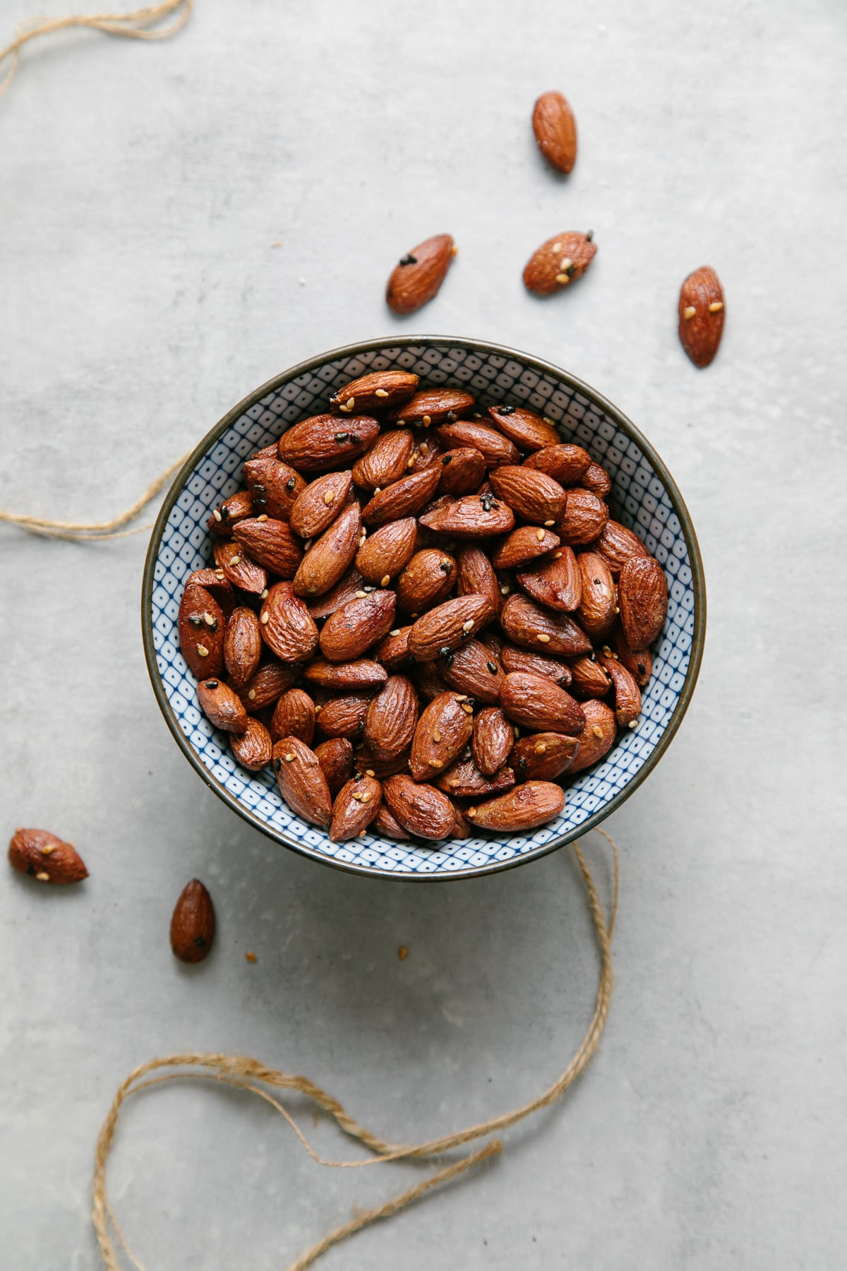 top down view of naturally sweetened roasted almonds in a blue and white bowl.