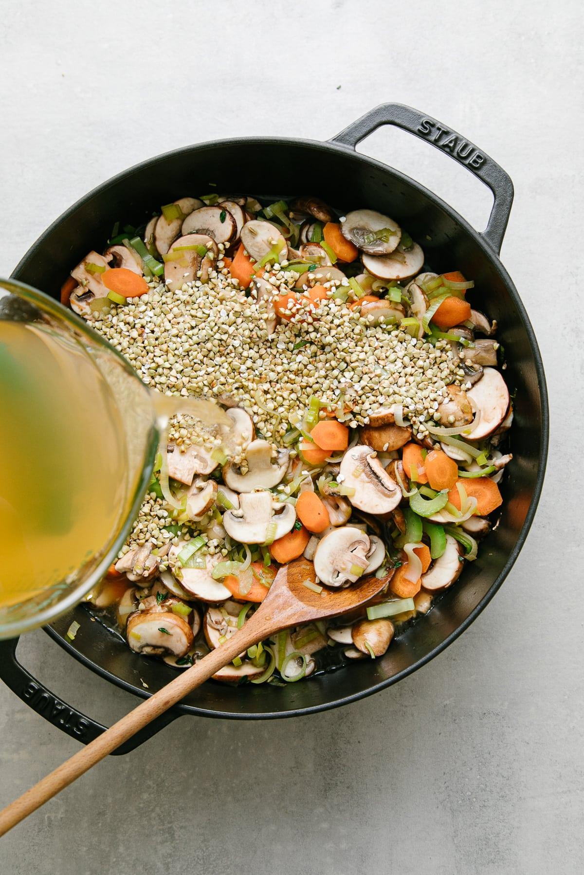 top down view showing the process of adding liquids to pot of veggies to make mushroom buckwheat soup.