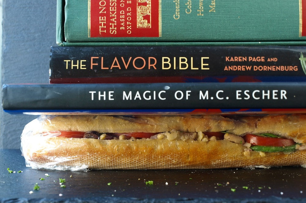 head on view of sandwich wrapped in saran and topped with 3 heavy books to help mash the sandwich.