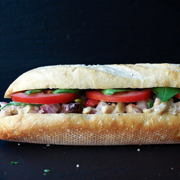head on view of pan bagnat white bean nicoise salad sandwich.