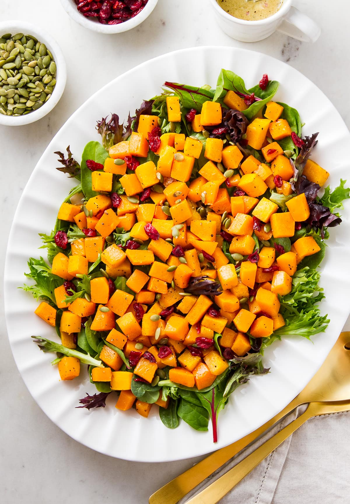 top down view of butternut squash salad with cranberries and shallot vinaigrette on a serving platter.