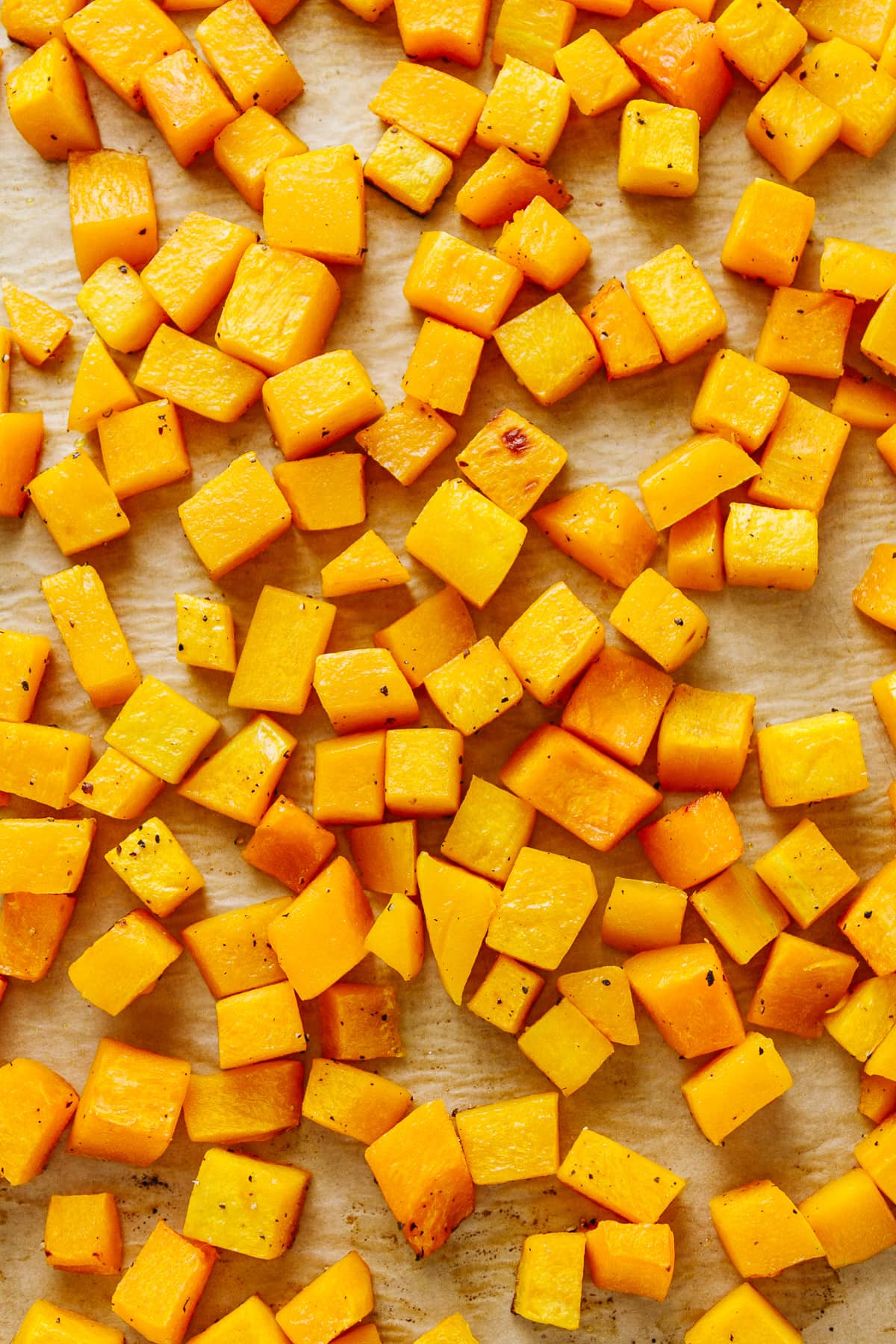top down view of freshly roasted butternut squash on a rimmed baking sheet.