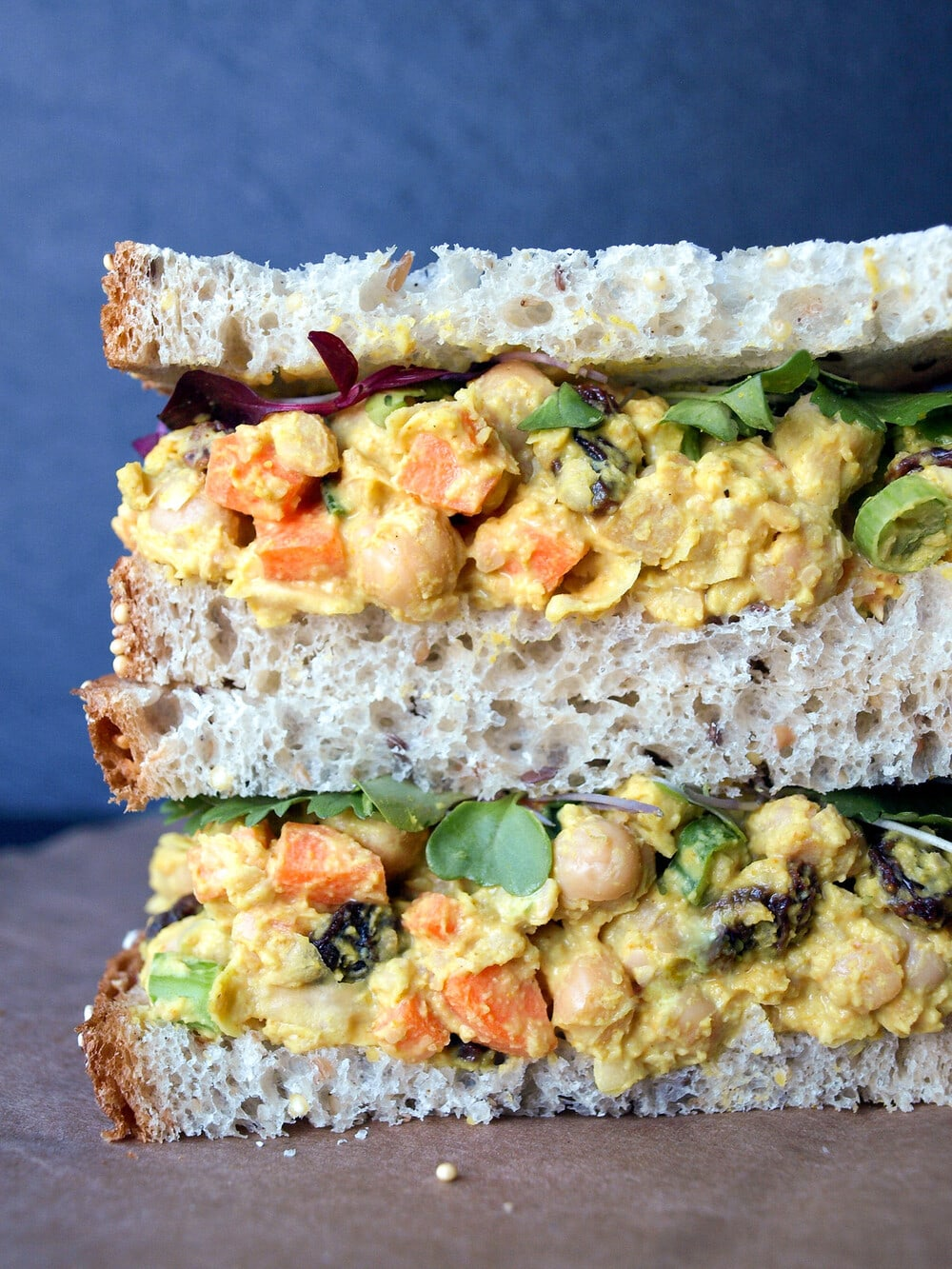 head on, up close view of curried chickpea chicken salad sandwich cut in half and stacked.
