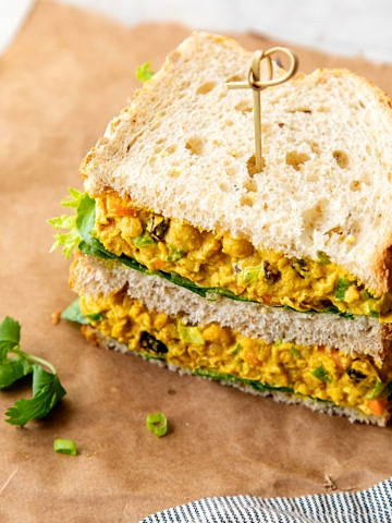 side angle view of curried chickpea salad sandwich sliced in half and stacked.