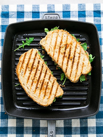 top down view of 2 grilled hummus sandwiches cooking on a cast iron griddle.