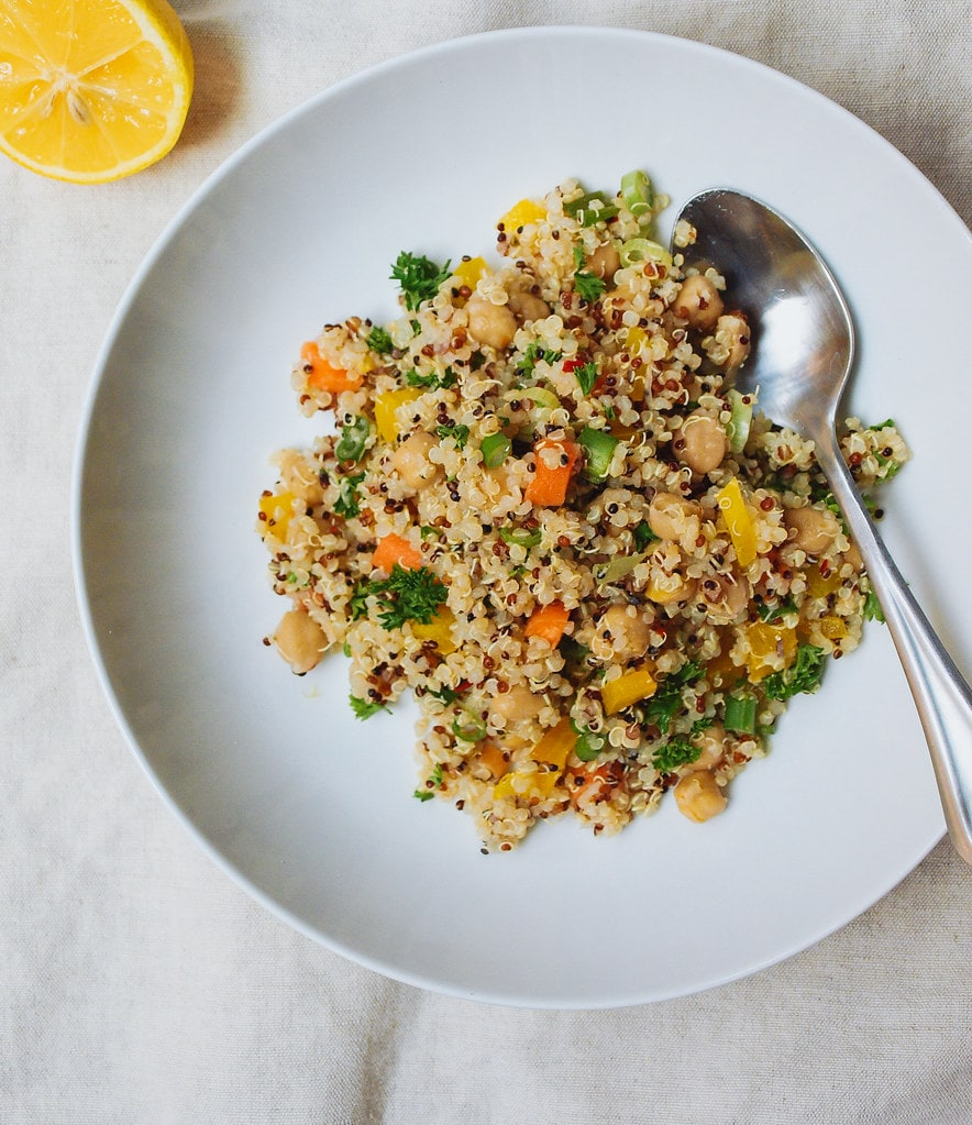 top down view of lemon quinoa chickpea salad in a white bowl with spoon