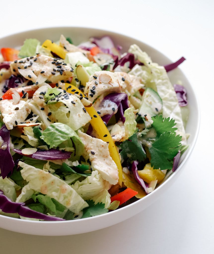 chinese chop salad in a white bowl on a white background