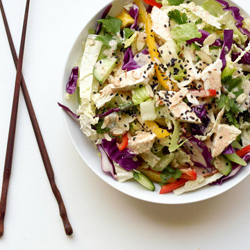 chinese chop salad with tofu in a white bowl with wooden chopsticks