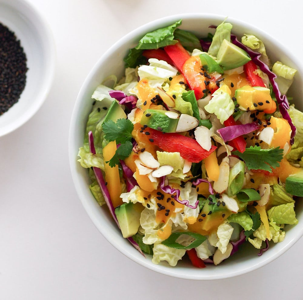 rainbow salad with mango dressing in a white bowl