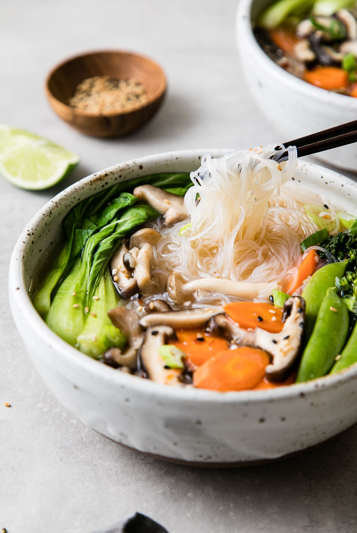 side angle view of healthy miso noodle bowl with chopsticks and items surrounding.