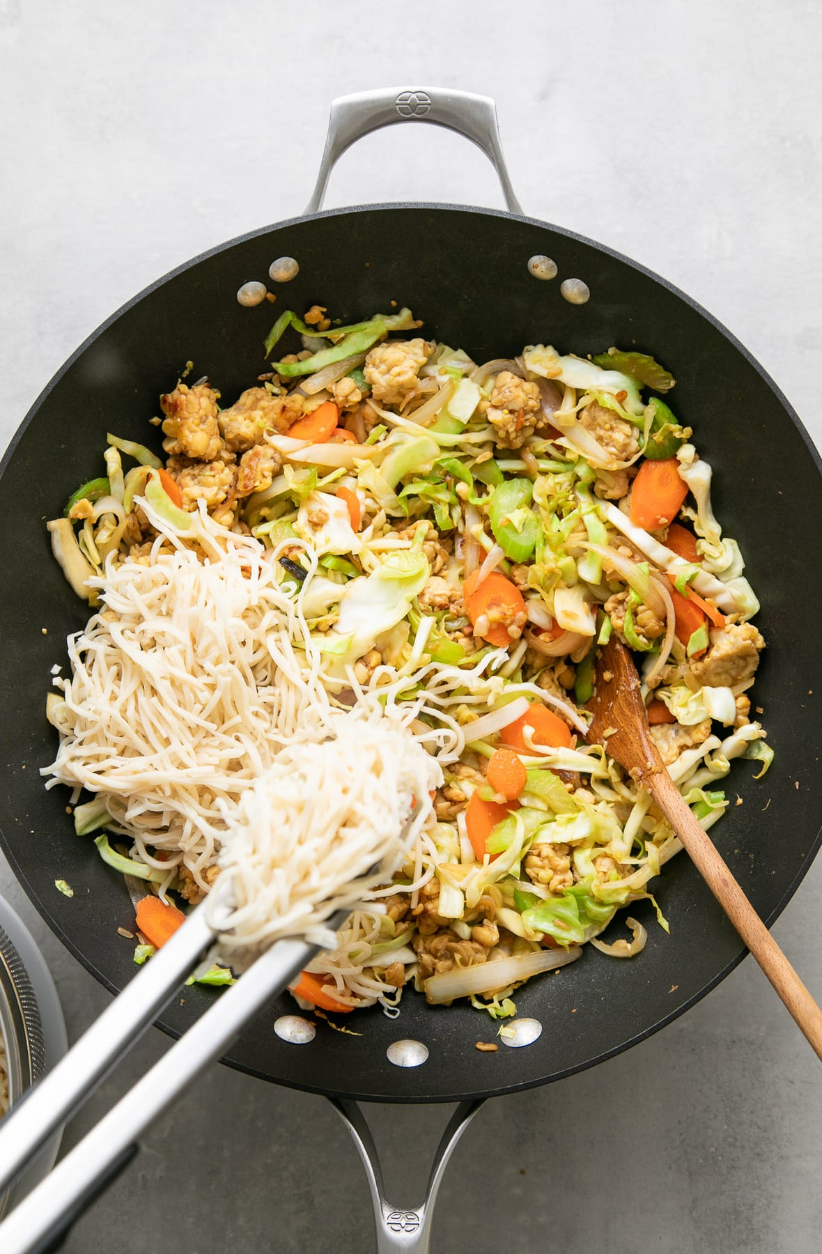 top down view of noodles added to chow mein vegetables.
