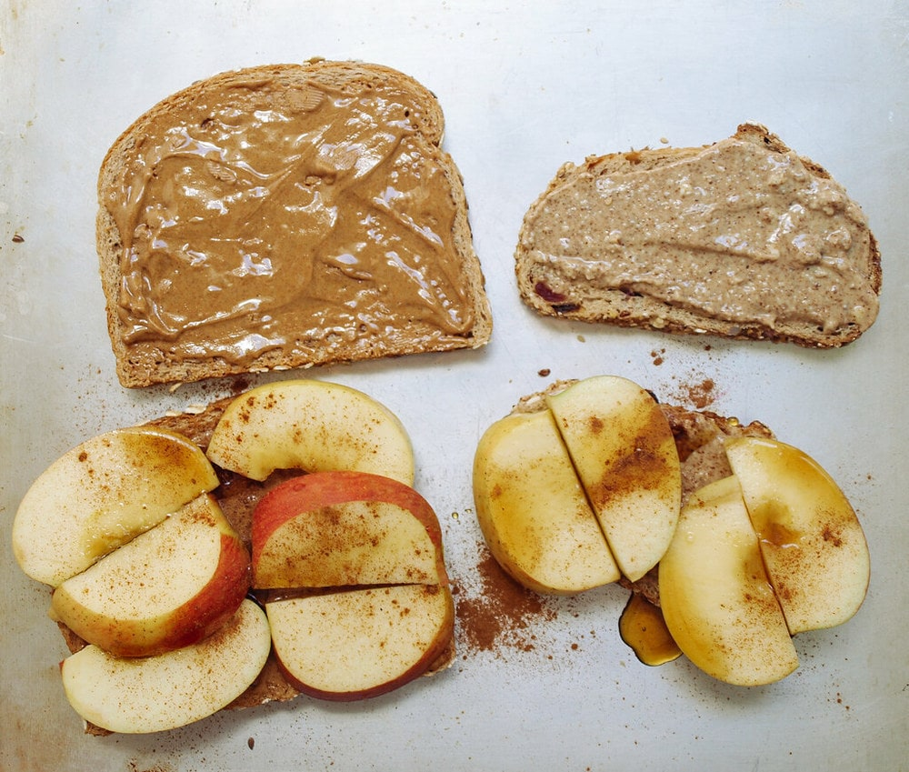 open faced grilled peanut butter and apple sandwiches on a cookie sheet