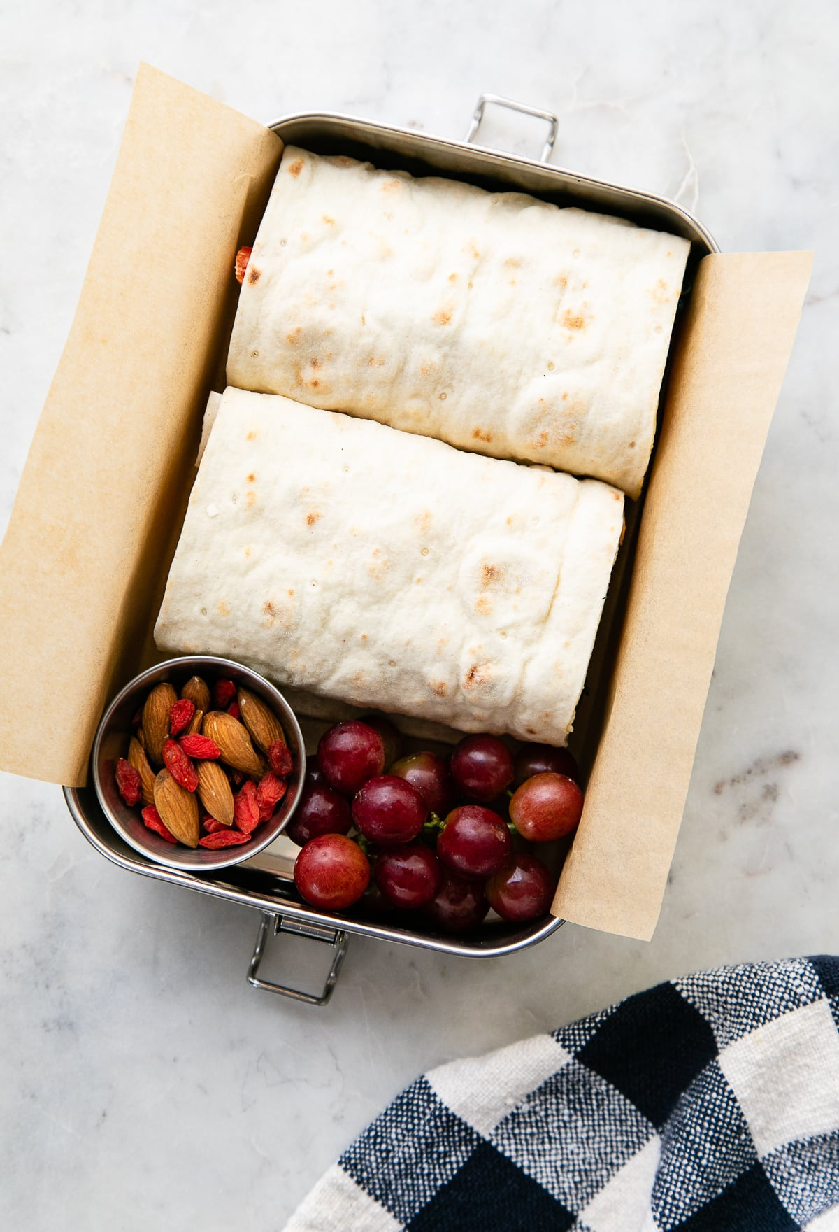 top down view of metal bento box with hummus veggie wrap, grapes and nuts.