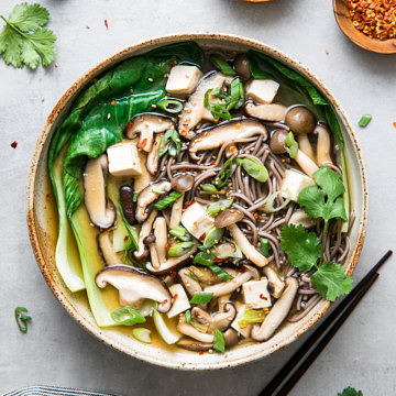 top down view of a bowl with serving of soba noodle soup with bok and mushrooms.