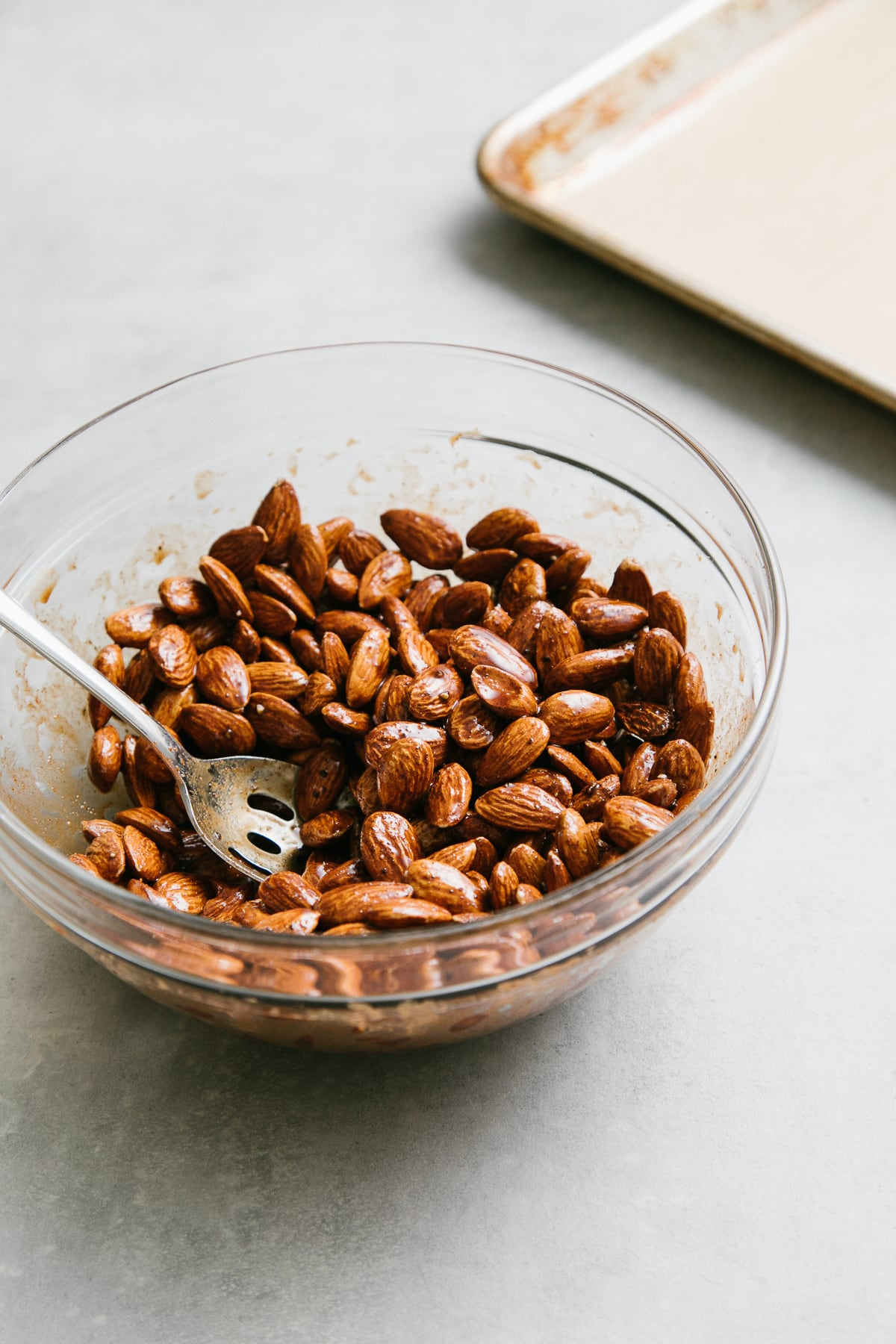 side angle view showing the process of mixing almonds with chocolate chai glaze in a glass mixing bowl.