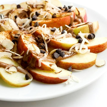 apple sliced topped with peanut butter, coconut, chocolate chips and cinnamon
