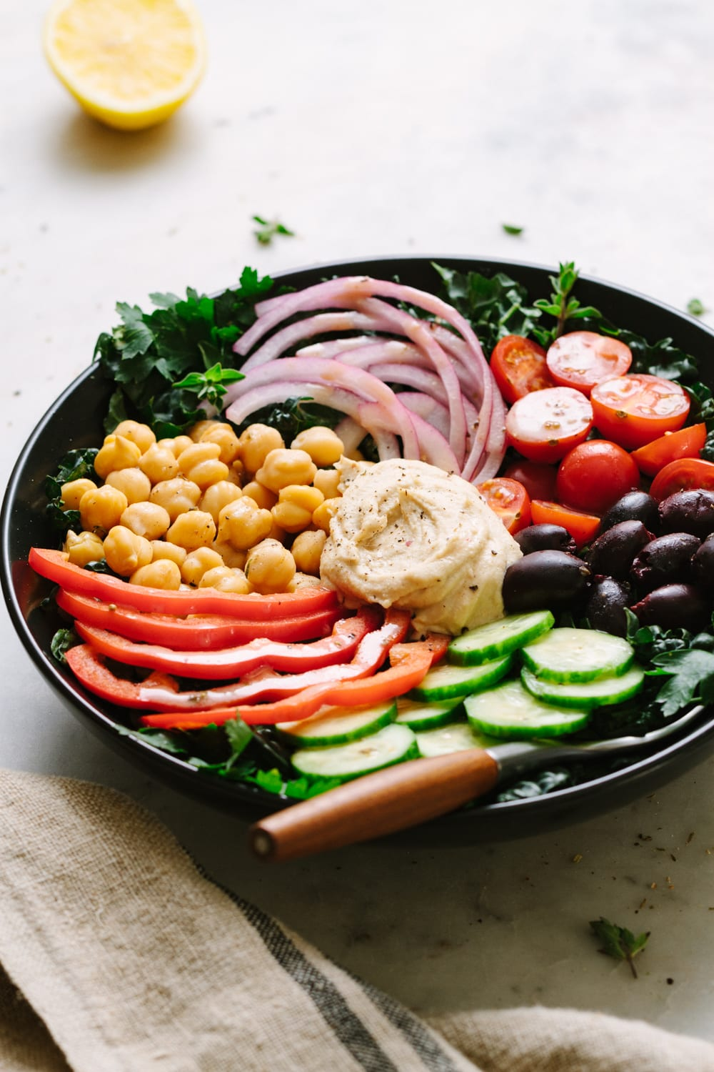 side angle view of black bowl with serving of healthy mediterranean kale salad.