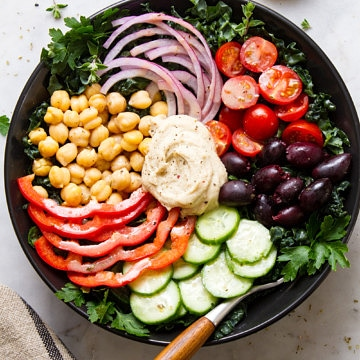 top down view of mediterranean kale salad in a black bowl.