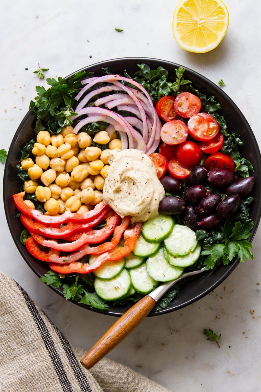 top down view of mediterranean kale salad in a black bowl.