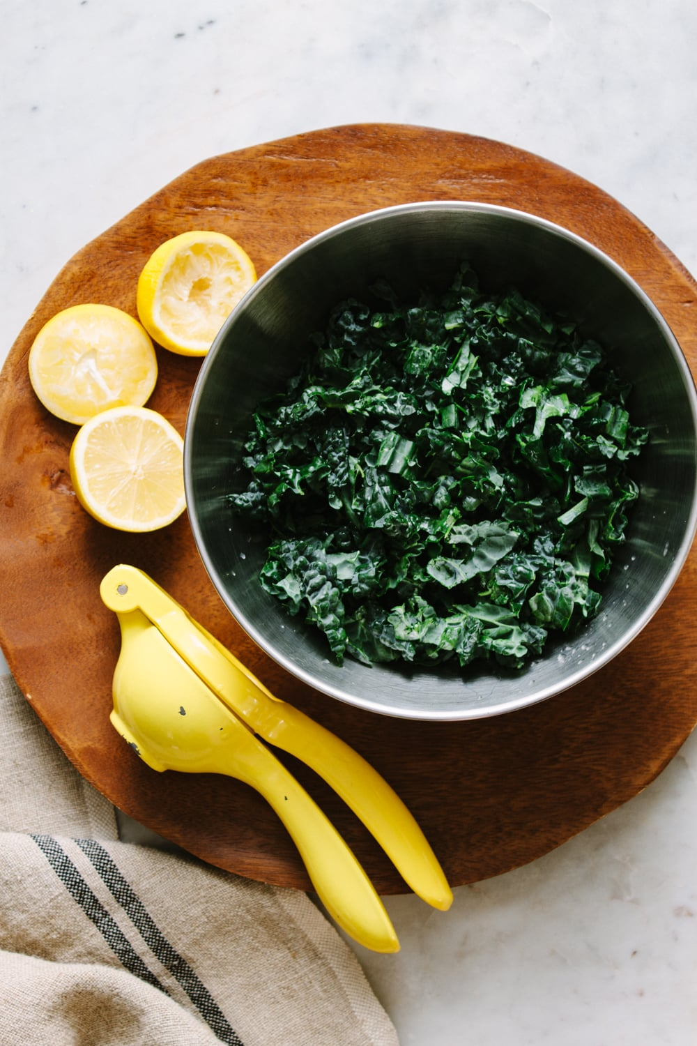 top down view of kale marinating with lemon in a stainless steel bowl.