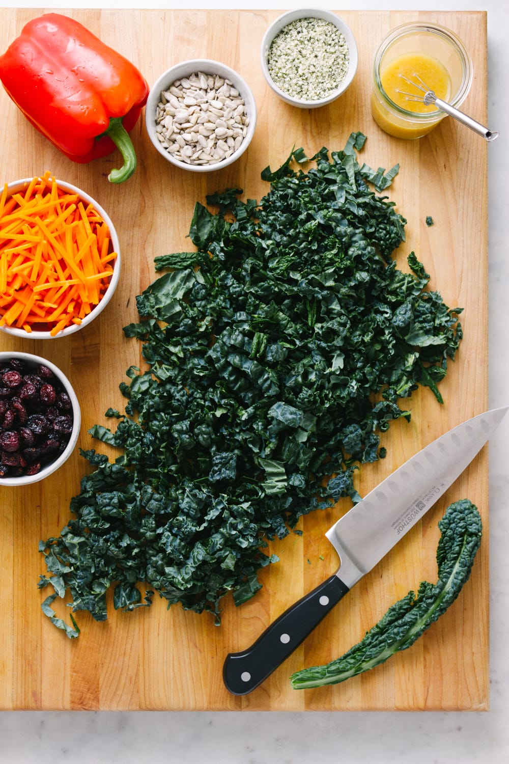 top down view of ingredients for kale salad with cranberries on a wooden cutting board.