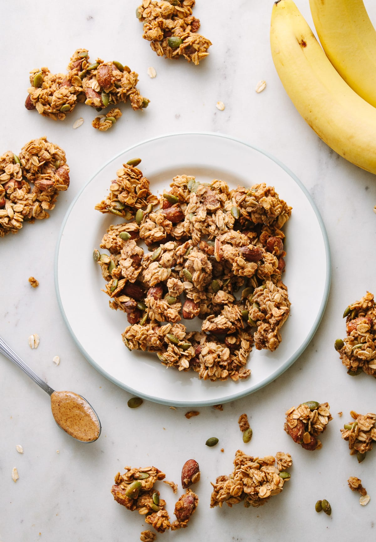 top down view of peanut butter banana granola clusters on a plate, surrounded by items.