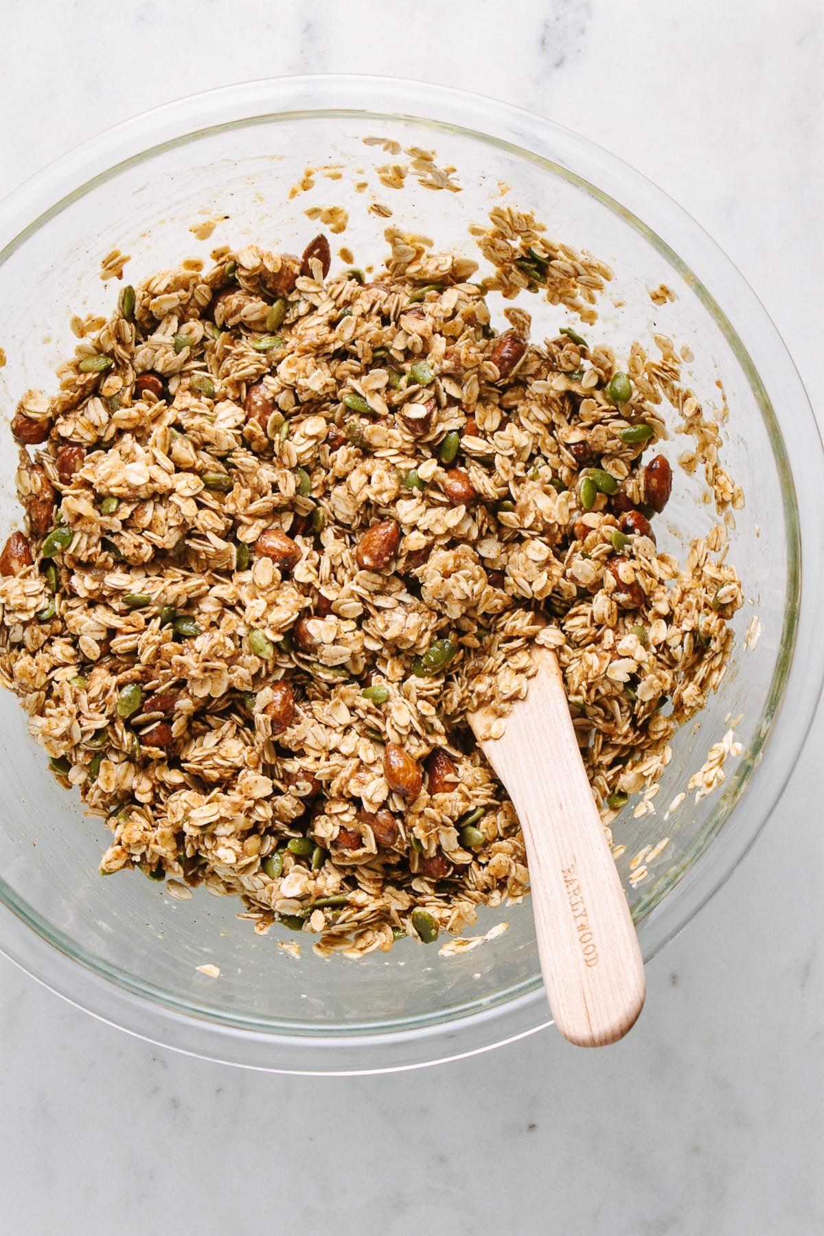 top down view of all ingredients to make peanut butter banana granola snack clusters mixed in a bowl.