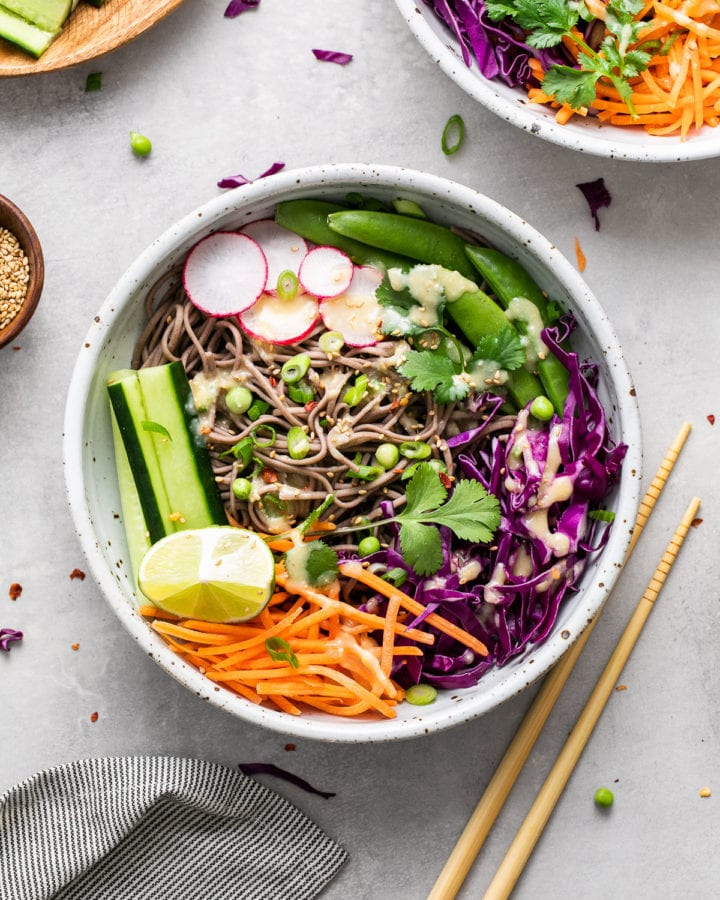 top down view of cold soba noodle bowl with with veggies and miso dressing and items surrounding.