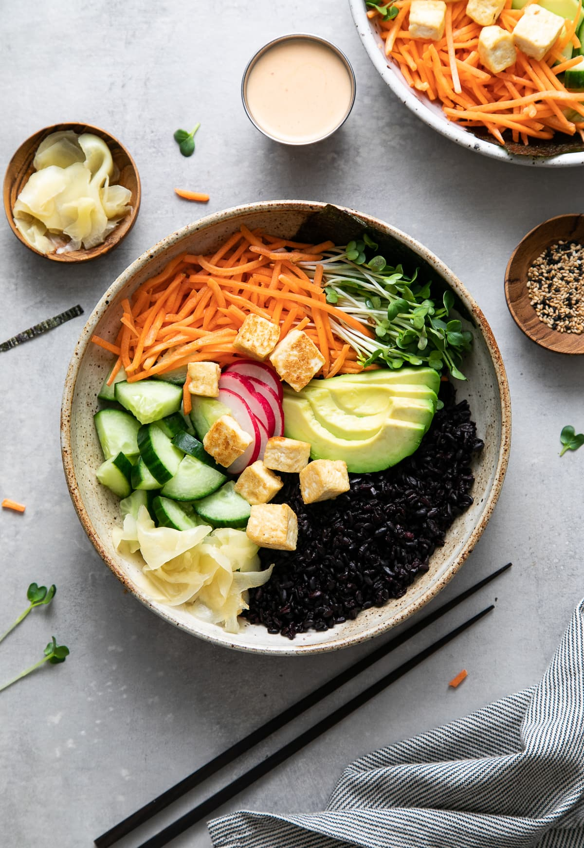 side angle view of freshly made vegan sushi bowl before adding creamy sauce with items surrounding.