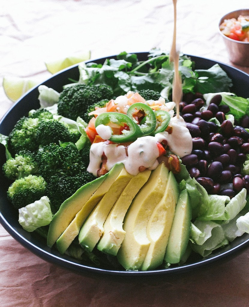 side angle view of broccoli, avocado and black bean salad with dressing being poured overtop.