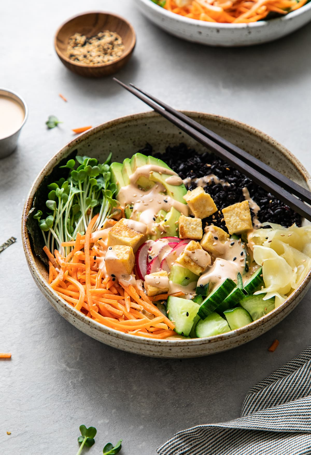 side angle view of vegan sushi bowl topped with creamy dynamite sauce with items surrounding.