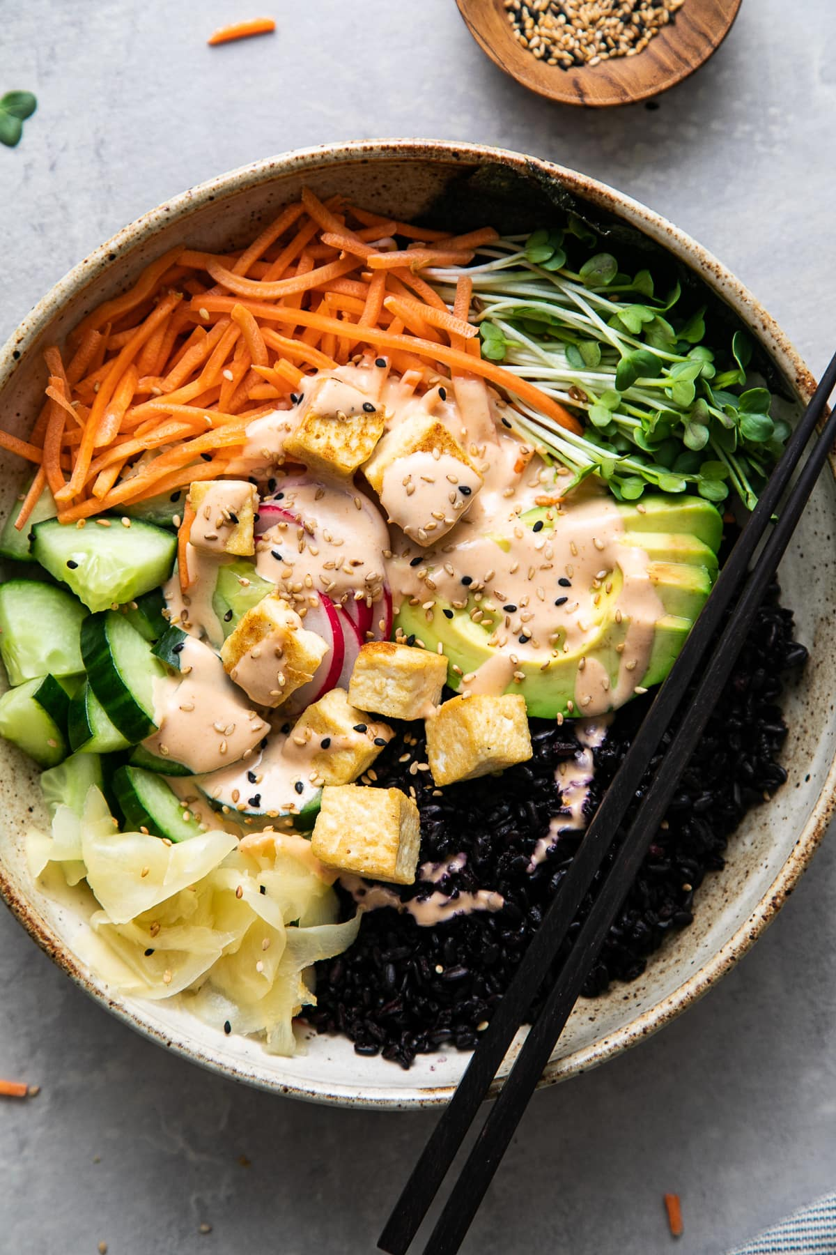 top down view of sushi bowl with chopsticks.