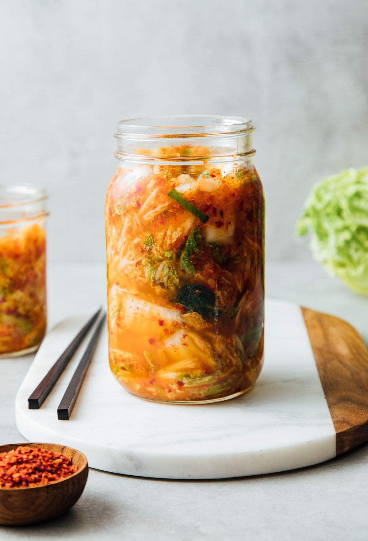 head on view of freshly fermented kimchi added to mason jar with items surrounding.