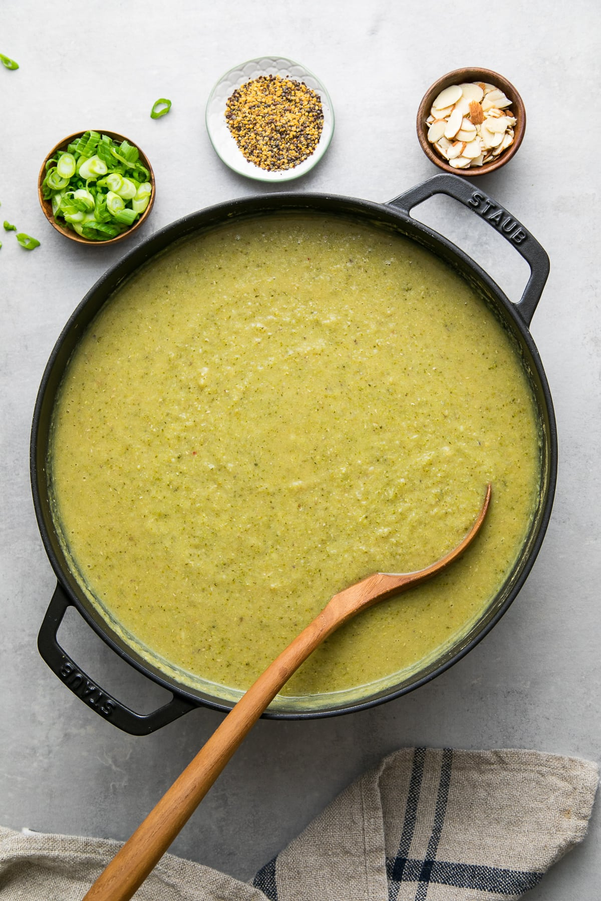 top down view of freshly made pot of vegan broccoli red lentil soup with items surrounding.