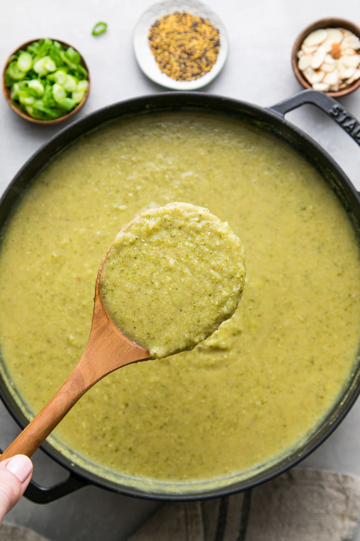 top down view of spoonful of creamy broccoli soup.