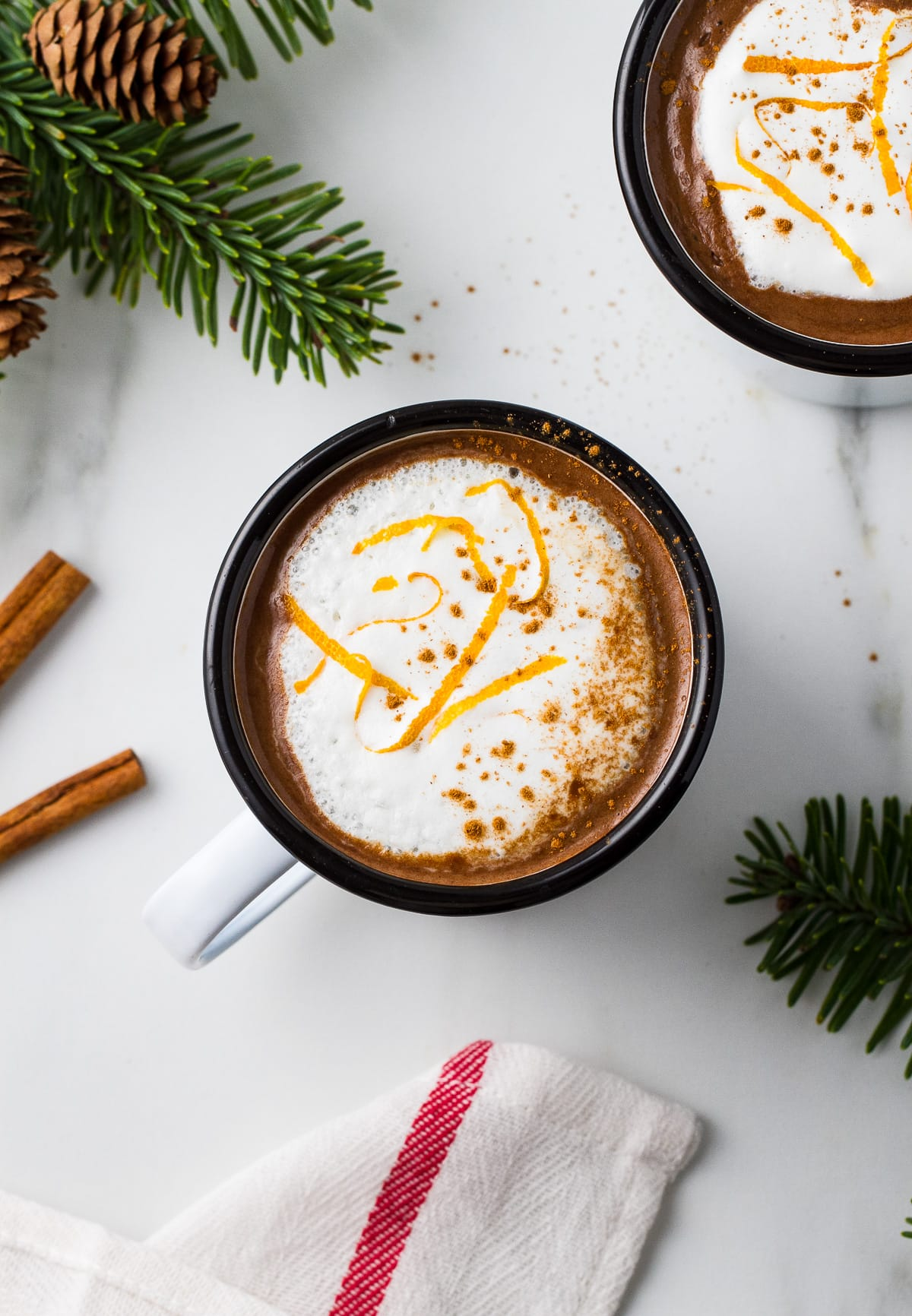 top down view of a orange hot cocoa in a white mug with black rim and surrounded by items.