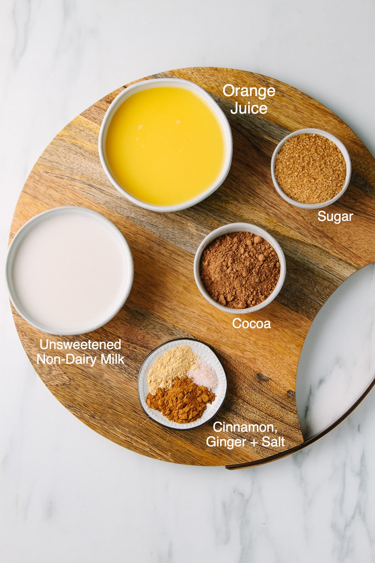 top down view of ingredients needed to make orange cocoa on a round, wooden serving board.