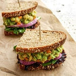 top down, side angle view of mashed avocado chickpea salad sandwich sliced in a half.