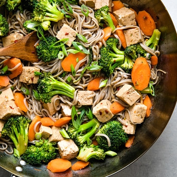 top down view of wok with freshly made soba noodle stir fry with tofu, broccoli and carrots.