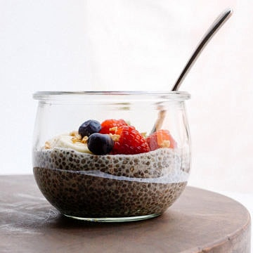 head on shot of a glass jar filled half way with vanilla chia seed pudding and mixed fruit with spoon on wooden cutting board