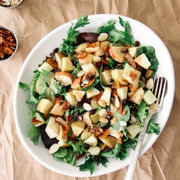 a bowl full of salad with crisp apples, leafy greens, coconut bacon, raisins and creamy almond butter dressing